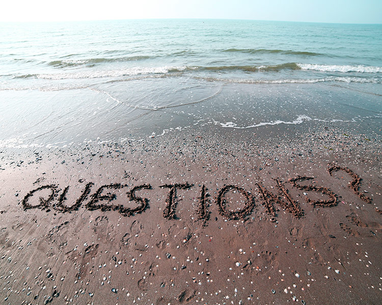 the word questions written on a sandy beach
