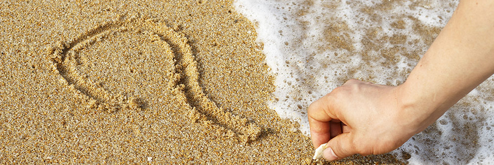 Hand drawing a question mark in the beach sand